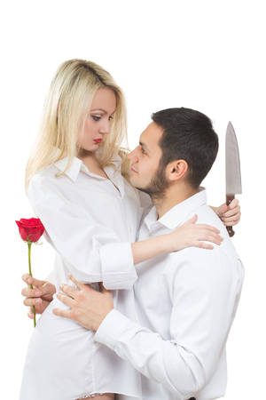 meanness: girl holding a knife traitor. man with a rose in his hand. on a white background Stock Photo
