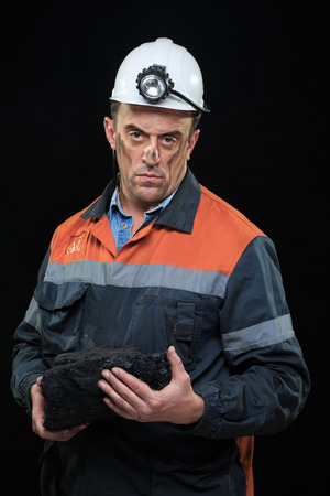 the miner: Coal miner showing lump of coal with thumbs up against a dark background Stock Photo