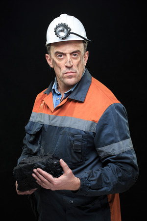 coal miner: Coal miner showing lump of coal with thumbs up against a dark background Stock Photo