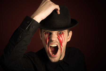 burgundy background: portrait of a man with bloody tears on burgundy background