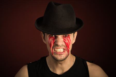 greet eyes: portrait of a man with bloody tears on burgundy background