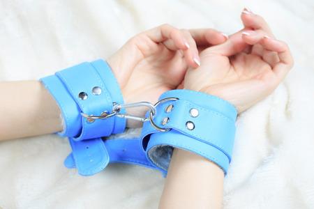 seks: vrouwelijke handen in lederen handboeien. gretig greep de lakens .. seksspeeltjes. passie Stockfoto