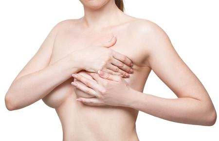 naked breast: Examining breasts. Close-up of young shirtless woman examining her breasts while standing against  white background