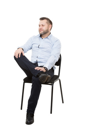 nonverbal communication: man sitting on chair. Isolated white background. foot on the leg