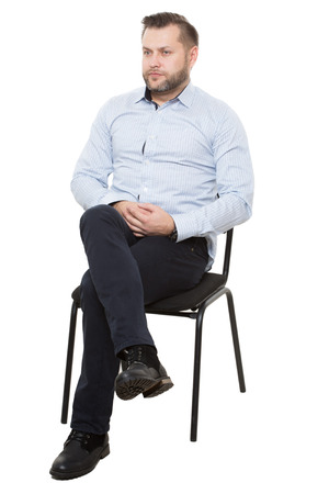 lack of confidence: man sitting on chair. Isolated white background