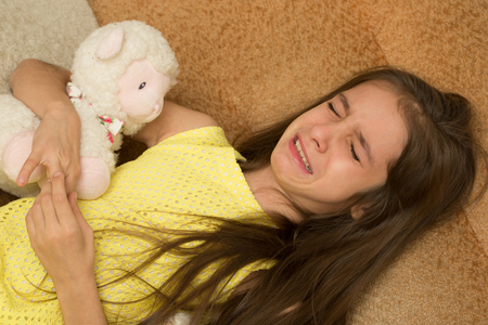 little girl crying on a chair. soft toy Stock Photo