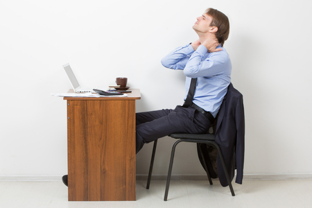 working stiff: Young Businessman Using Computer Suffering From Neck Ache Stock Photo