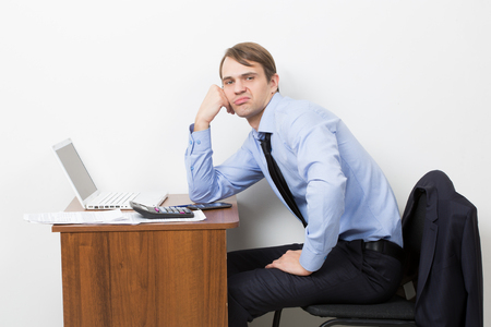 lean back: Office worker takes a break from his work. He is sitting with a sour face