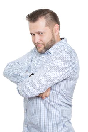 comunicacion no verbal: adulto de sexo masculino con una barba. aislado sobre fondo blanco. postura defensiva cerrada. brazos cruzados. lenguaje corporal