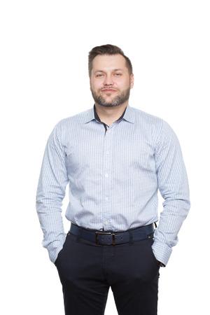 comunicacion no verbal: masculino con una barba. fondo blanco aislado. manos en los bolsillos. postura desconfianza