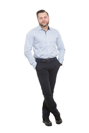 male with a beard. isolated on white background.hands in his pockets. legs crossed. body language.