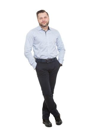 comunicacion no verbal: masculino con una barba. aislado en blanco background.hands en los bolsillos. piernas cruzadas. lenguaje corporal.