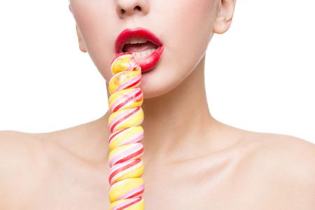 секс: Крупным планом выстрел из уст женщины с ярко-красными губами с леденцом Фото со стока