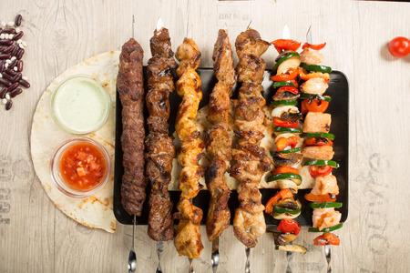 shashlik. kebab skewer on black plate. sauce and onions