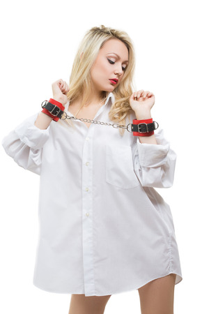 cuffs: Sexy beautiful blonde girl in handcuffs wearing white mens shirt isolated on white background Stock Photo