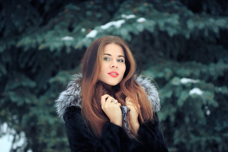 beautiful smiling girl on a background of trees. Winter portrait. coat with a hood