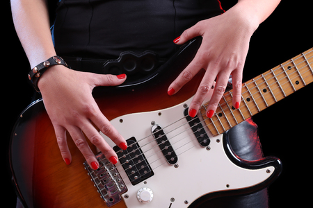 reflectance: female hand on the detail of a guitar in dark back. Stock Photo