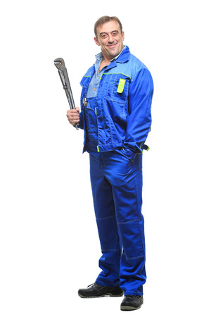 Full length portrait of happy male mechanic in overalls holding wrench over white background. Vertical shot. Zdjęcie Seryjne