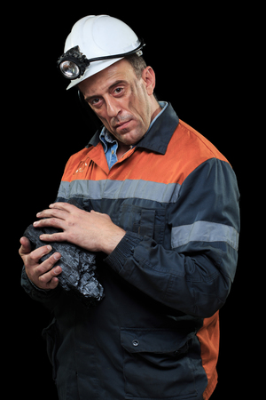 coal miner: Coal miner showing lump of coal with thumbs up against a dark Stock Photo