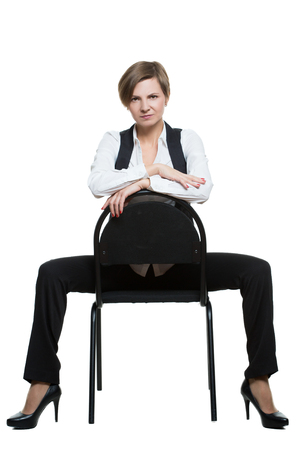 dominant woman: woman sits astride a chair. arms crossed. dominant position. Isolated on white background