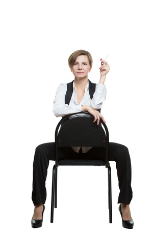 dominant woman: woman sits astride a chair. sexy shows wrist. dominant position. Isolated on white background