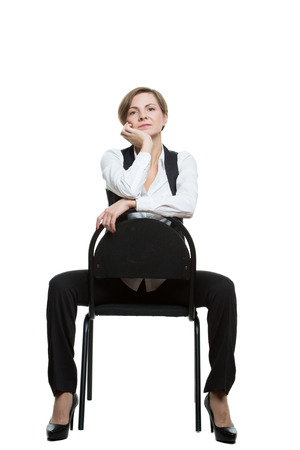 hand position: woman sits astride a chair. hand under chin. misses. dominant position. Isolated on white background