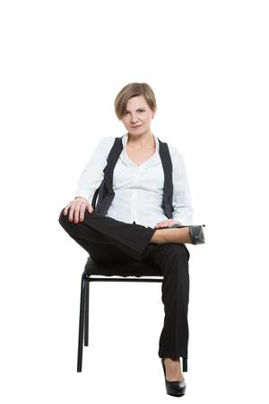 comunicacion no verbal: mujer se sienta a horcajadas en una silla. las piernas cruzadas y el brazo fijo. echa de menos. posición dominante. Aislado en el fondo blanco