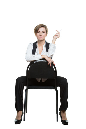 woman sits astride a chair. sexy shows wrist. dominant position. Isolated on white background