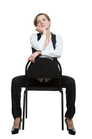 dominant woman: woman sits astride a chair. hand under chin. misses. dominant position. Isolated on white background