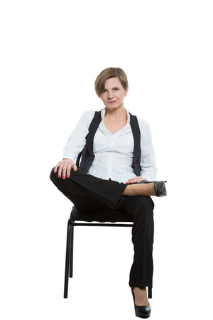 stubbornness: woman sits a chair. legs crossed, fixed arm. misses. dominant position. Isolated on white background