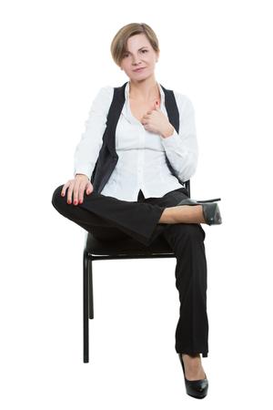 comunicacion no verbal: mujer se sienta a horcajadas en una silla. las piernas cruzadas, mano toca el pecho. gesto seductor. posici�n dominante. Aislado en el fondo blanco