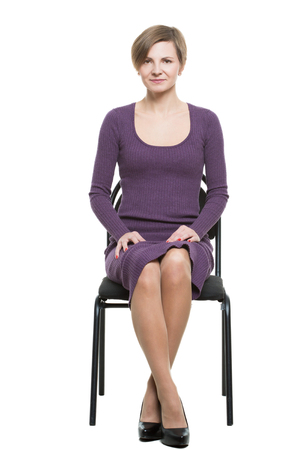 enticing: woman sits a chair. enticing gesture. expresses excitement. crossed ankles, elbows pressed. Isolated on white background. body language