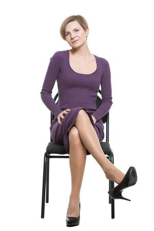 Frau sitzt einen Stuhl. Pose, die das sexuelle Verlangen. Flirten. Beine gekreuzt, Schuhtropfen. Biegen. Isoliert auf weißem Hintergrund. Körpersprache Standard-Bild - 48647874