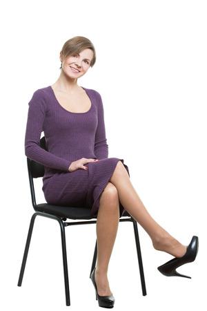 comunicacion no verbal: mujer se sienta una silla. plantean que muestra el deseo sexual. flirteador. las piernas cruzadas, las gotas de calzado. flexi�n. Aislado en el fondo blanco. lenguaje corporal
