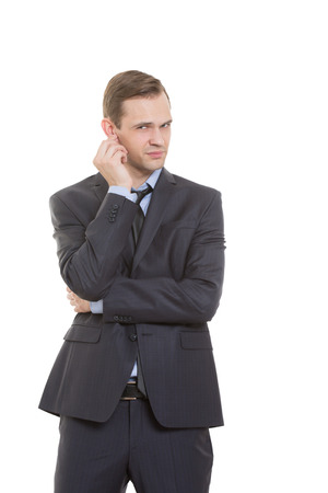 comunicacion no verbal: lenguaje corporal. hombre en traje de negocios aislados sobre fondo blanco. rascarse, frotarse la oreja. gesto de desconfianza altavoz Foto de archivo