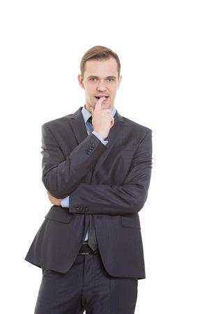 comunicacion no verbal: lenguaje corporal. el hombre en traje de negocios aislado fondo blanco. dedo en la boca. un gesto de incertidumbre, la necesidad de aprobaci�n y el apoyo Foto de archivo