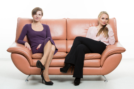 finger in mouth: beautiful female friends on the sofa. two businesswomen. body language, gestures psychology. paired gestures. Stock Photo
