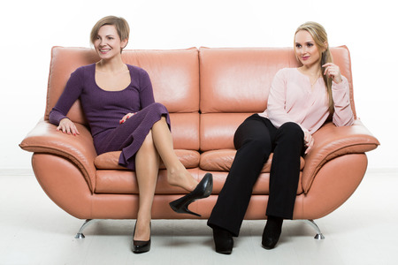 foots: beautiful female friends on the sofa. two businesswomen. body language, gestures psychology. paired gestures. Stock Photo