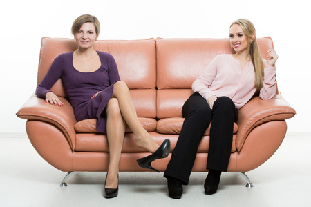 perineum: beautiful female friends on the sofa. two businesswomen. body language, gestures psychology. paired gestures. Stock Photo