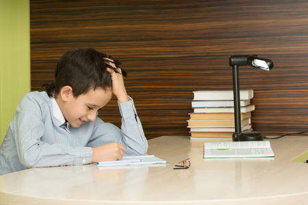 the pupil: beautiful brunette. Pupil elementary school does homework.