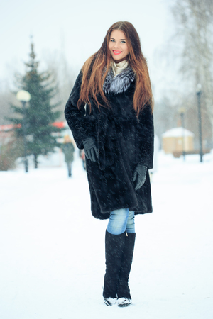 topcoat: beautiful smiling girl on a background of trees. Winter portrait. coat with a hood