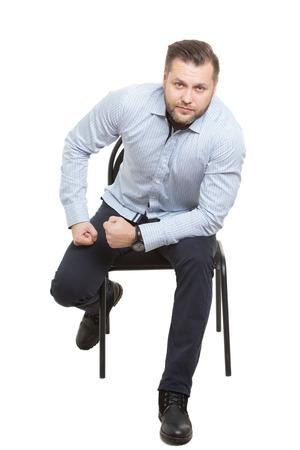 comunicacion no verbal: Hombre sentado en la silla. Fondo blanco aislado. gesto de preparaci�n para la acci�n. posici�n inicial Foto de archivo