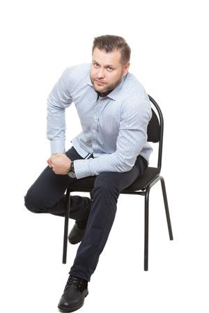 comunicacion no verbal: Hombre sentado en la silla. Fondo blanco aislado. gesto de preparación para la acción. posición inicial Foto de archivo