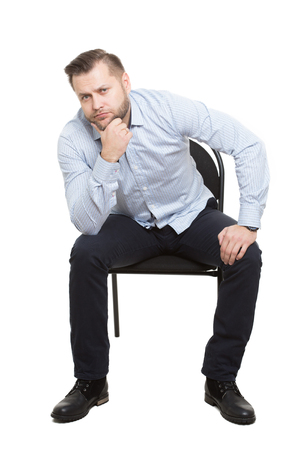 Hombre sentado en la silla. Fondo blanco aislado. Lenguaje corporal. gesto.