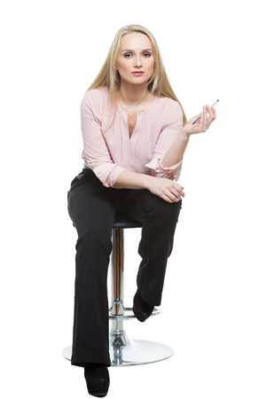 'phallic symbol': Elegant beautiful woman sitting on a contemporary metal bar stool.  isolated on white Stock Photo
