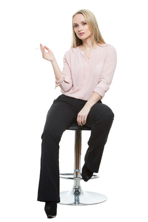 phallic symbol: Elegant beautiful woman sitting on a contemporary metal bar stool.  isolated on white Stock Photo