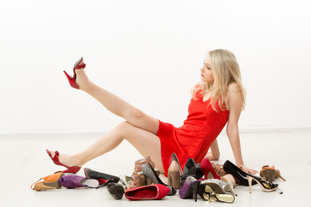 girl in red dress sitting on the floor. Selects shoes. Trying on shoes. Stock Photo