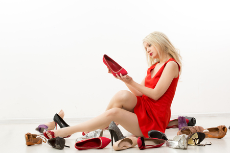 girl in red dress sitting on the floor. Selects shoes. Trying on shoes. 스톡 콘텐츠