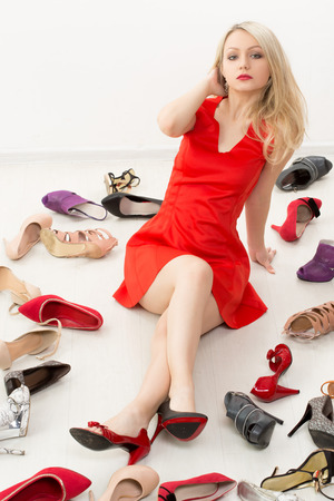 heel strap: girl in red dress sitting on the floor. Selects shoes. Trying on shoes. Stock Photo