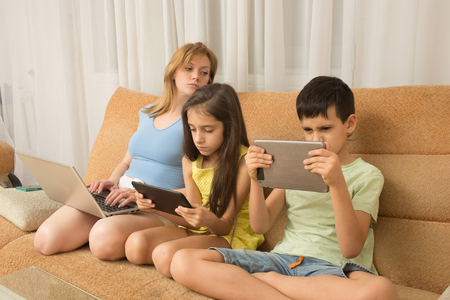 addiction: mother, daughter, son with laptop and tablet pc Stock Photo